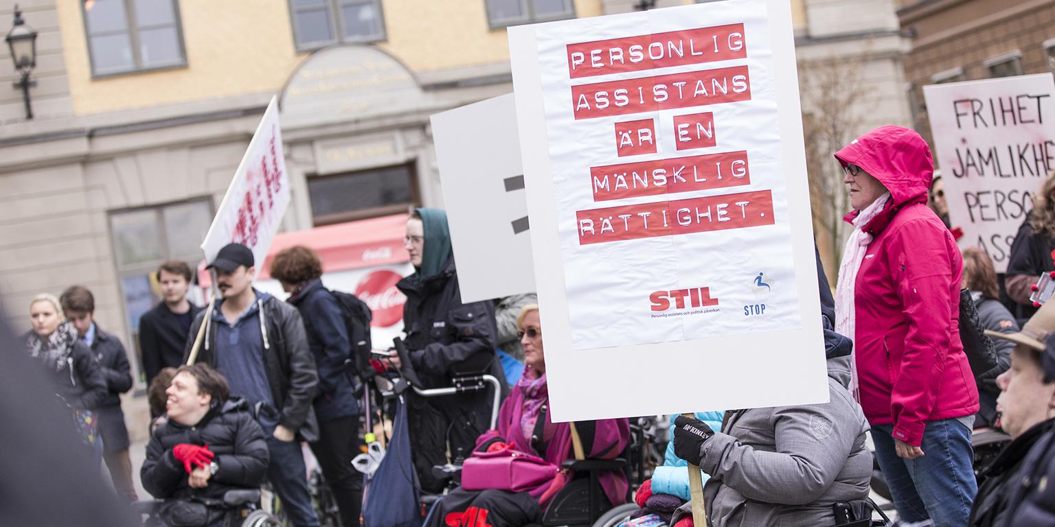 """Foto från en demonstration. På ett plakat står det """"personlig assistans är en mänsklig rättighet"""""""