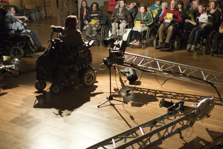 En assistansanvändare står med ryggen mot kameran på en upplyst scen. Många av de i publiken har rullstol.