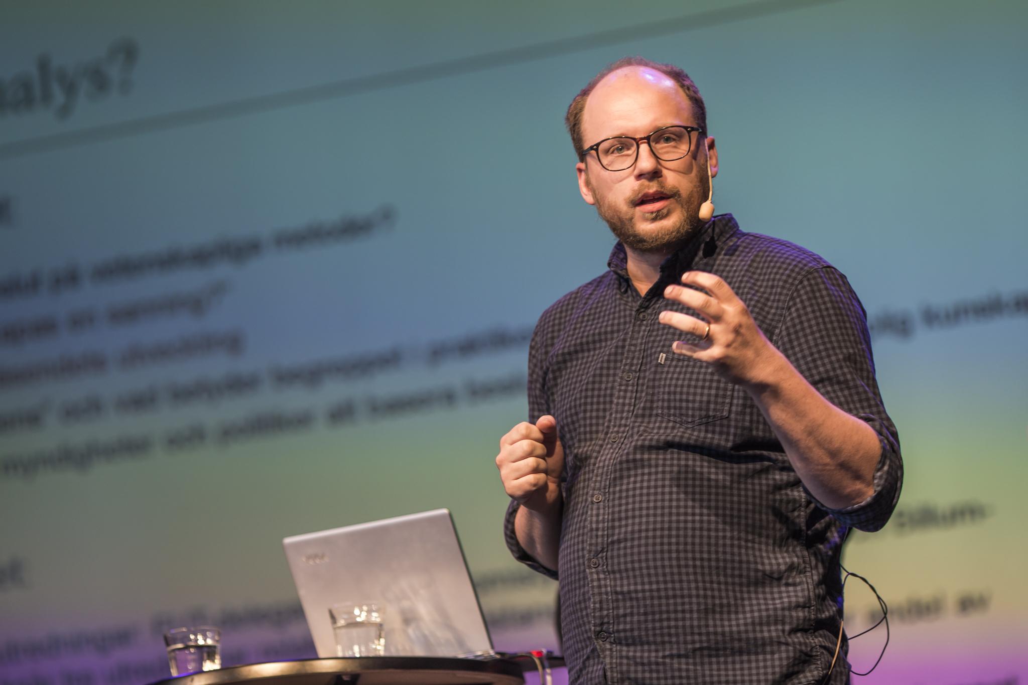 Bild på Niklas Altermark som håller på att förklara något på en scen.