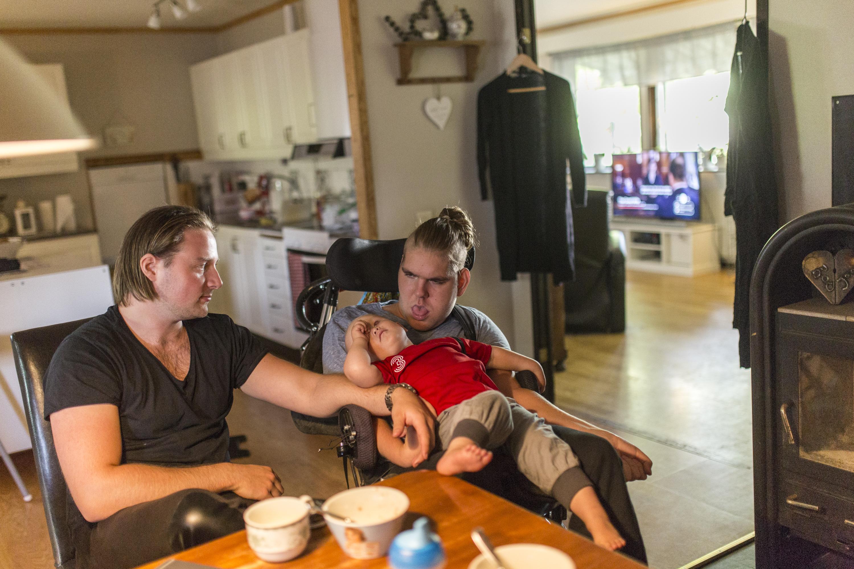 En av STILs arbetsledare sitter runt sitt köksbord. I famnen har har en liten bebis. Bredvid honom sitter hans assistent.