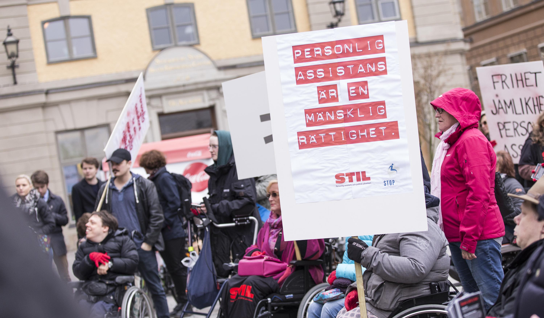 """Foto från en demonstration på Mynttorget i Stockholm. Flera personer syns i bilden, några använder rullstol. En person håller i en skylt där det står """"personlig assistans är en mänsklig rättighet"""""""