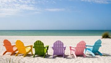 Färgglada solstolar på en sandstrand
