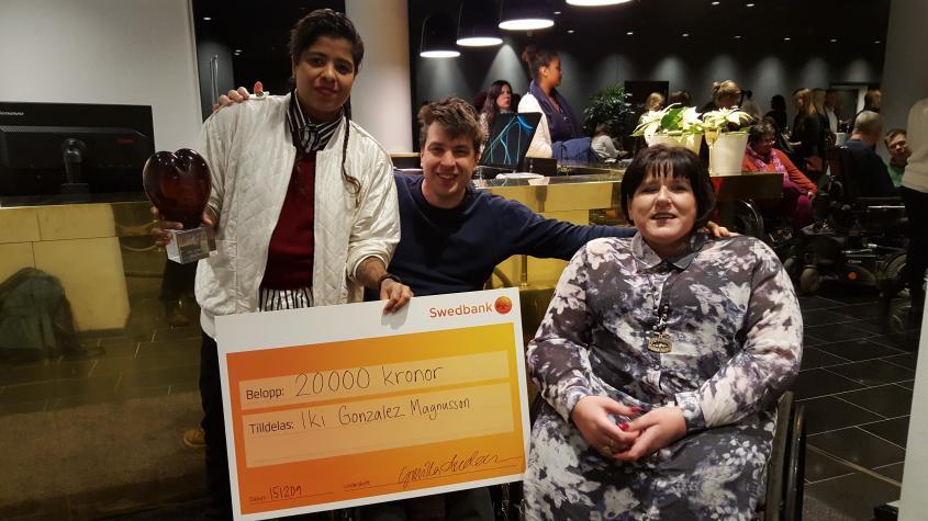 2015 års STIL-prismottagare Iki Gonzalez Magnusson tillsammans med Jonas Franksson och Veronica Kallander från STILs styrelse. Iki håller i sin prischeck. I bakgrunden syns minglande personer.