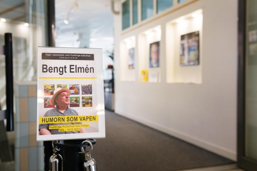 Affisch på Bengt Elmén för hans utställning Humorn som vapen. Bakom affischen skymtar början på utställningen.