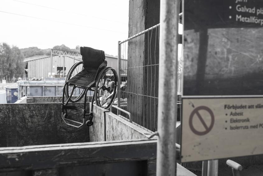 Svart-vit av en tom rullstol på kanten av en container på soptipp