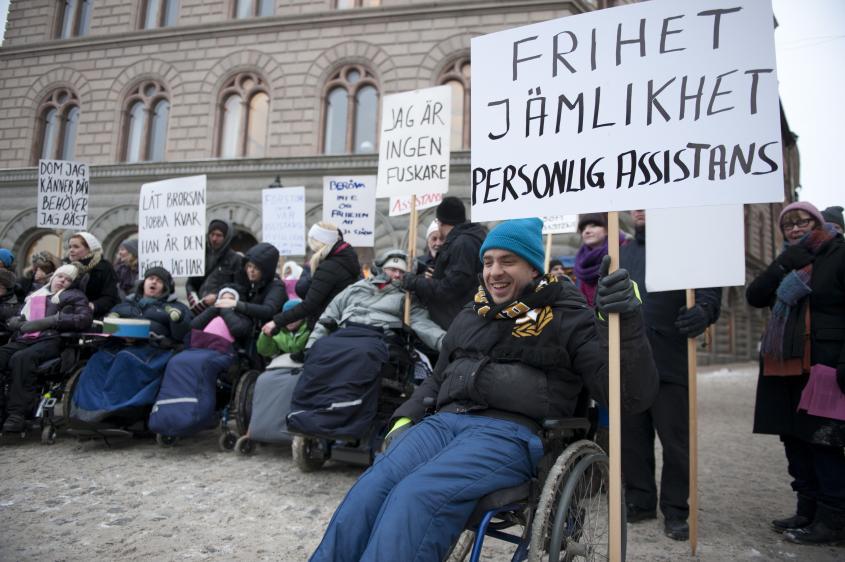 """Bild från en demonstration. Flera personer klädda i varma vinterkläder håller i skyltar. Närmast syns Jonas Franksson med en skylt där det står """"frihet, jämlikhet, personlig assistans"""""""