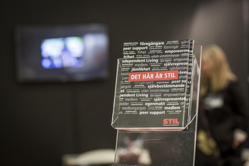 """En broschyr står i ett ställ mot svart bakgrund. På broschyren står det """"det här är STIL""""."""