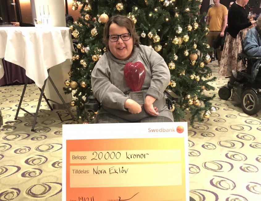 Nora Eklöv med priset, ett hjärta i rött glas och en prischeck på 20000 kronor