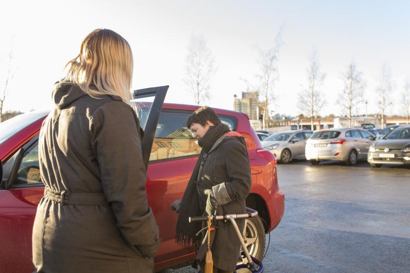 En arbetsledare kliver in i sin bil med stöd av sin assistent