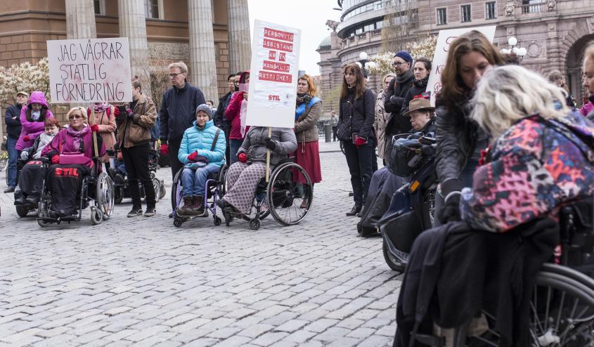 """Bild från en demonstration. Många personer på Mynttorget i Stockholm. Två skyltar syns: """"Jag vägrar statlig förnedring"""" och """"Personlig assistans är en mänsklig rättighet""""."""