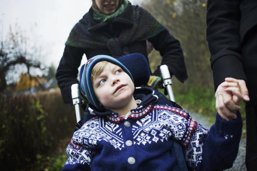 Ett barn promenerar med sin mamma och håller henne i handen. Bakom går assistenten och kör rullstolen.