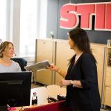 Bild från STILs reception. En av STILs anställda räcker över papper till den som sitter i receptionen.