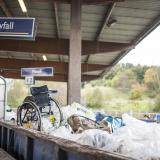 """En tom rullstol står i en sopcontainer på soptippen. Vid sidan av finns en skylt där det står """"Restavfall""""."""