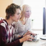 Två personer sitter framför en datorskärm.