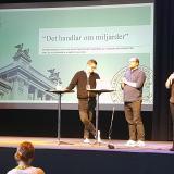 """Niklas Altermark och Hampus Nilsson står på scenen framför en skärm med bilden """"Det handlar om miljarder""""."""